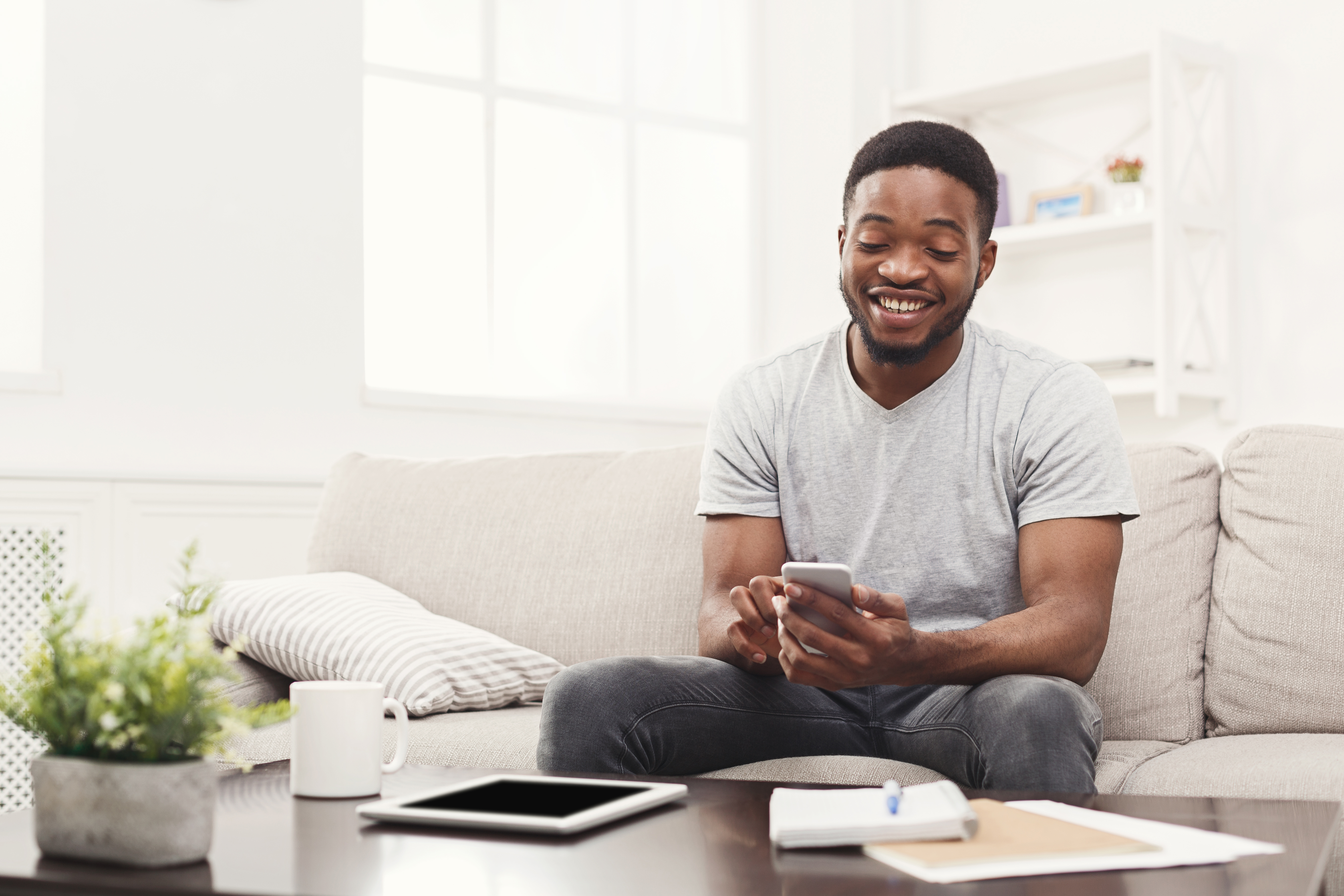 Man on couch at home checking out his phone