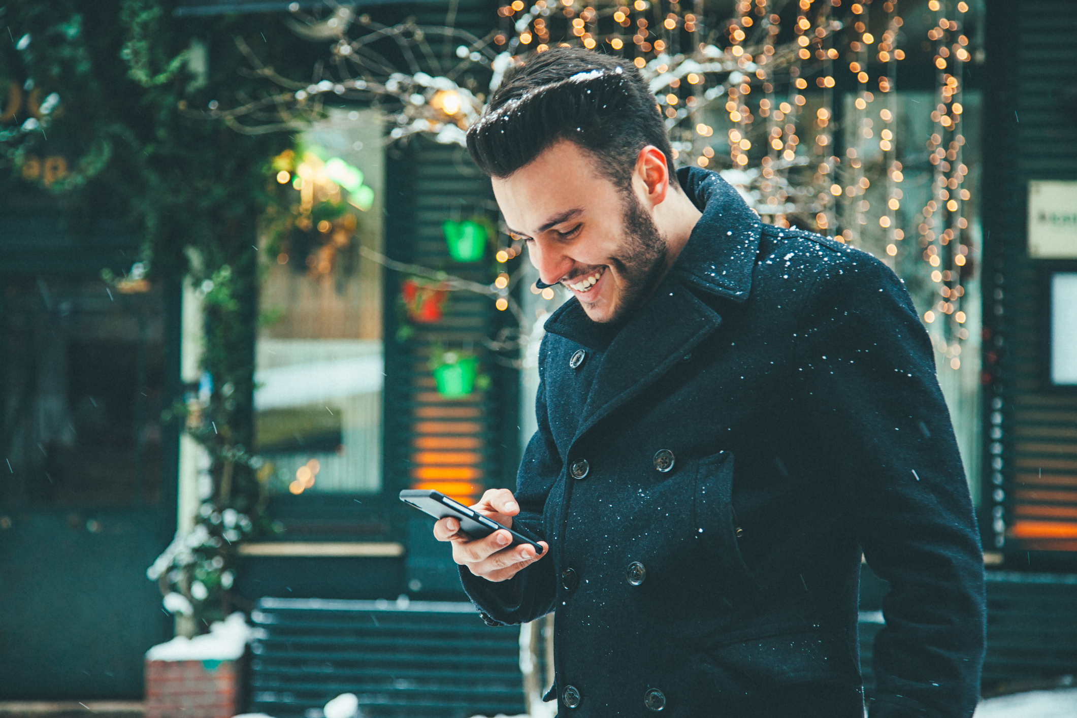Man wearing winter coat outdoors using smartphone