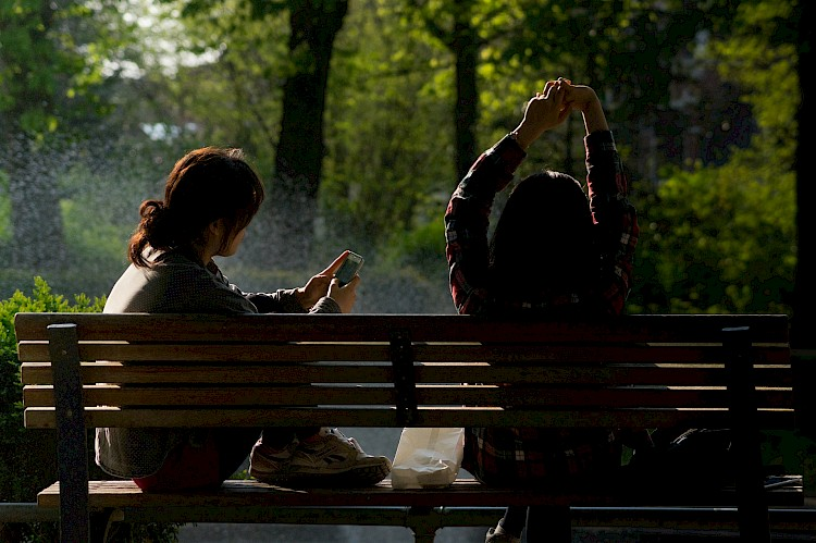 Woman sits on park bench next to friend and uses smartphone