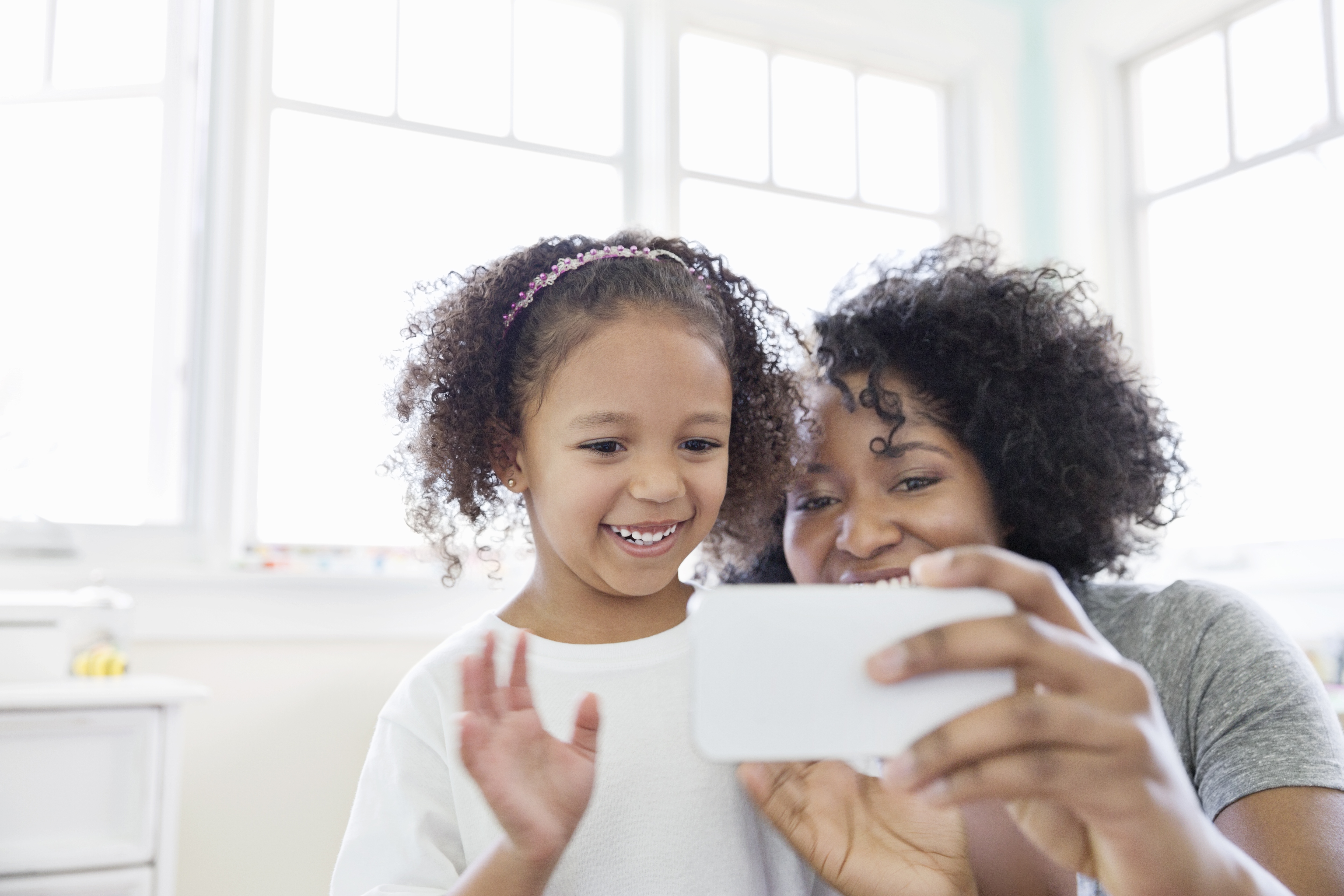 Mother and daughter smiling at phone